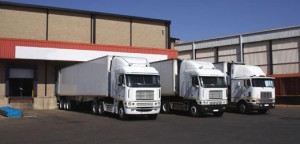 three white trucks in front of a storage house