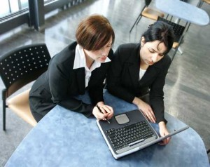 two women working on a laptop
