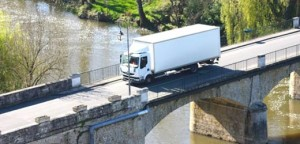 truck passing a stone old bridge